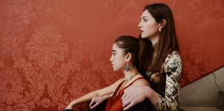 Two girls sit facing away from the camera in front of a red wall