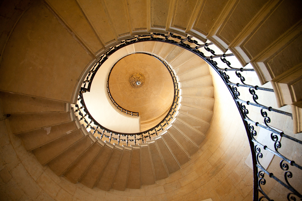 A shot of a grand, stone spiral staircase looking from the bottom up.