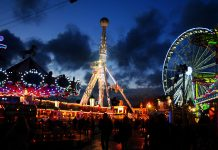 holiday theme park in london at night with many lit-up multicoloured rides