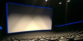 A large empty cinema with black seats facing a large blank screen