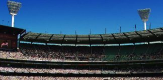 The green grass of the MCG with players wearing white test kit and the stands with the crowd in the background