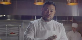 David Chang stands in a kitchen wearing his chef uniform