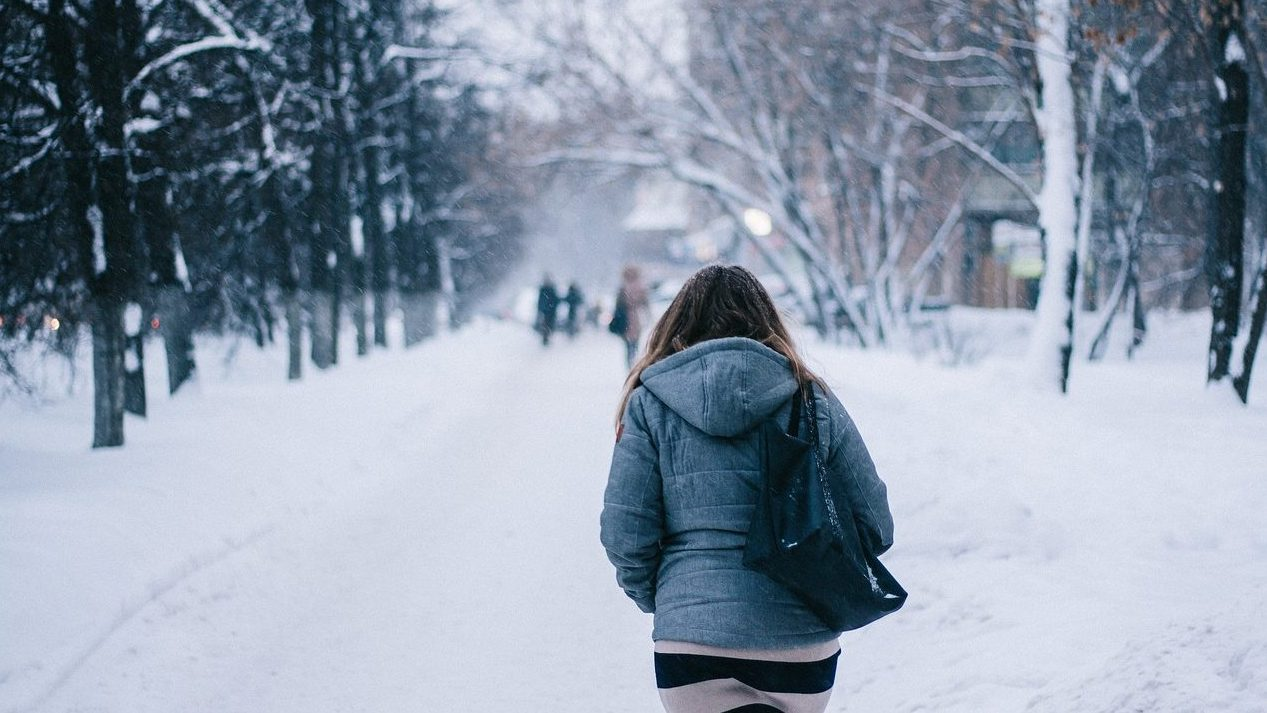 A woman walks down a snowy path with trees lining it. She is wearing a coat and carries a black bag over her shoulder.