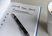 pen on paper about to write new year's resolutions with coffee