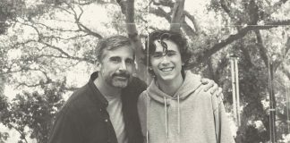 A middle-aged man and a teenage boy smile into the camera. The man has his arm around the boy.
