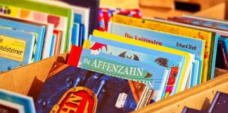 a stack of children's books in a wooden box