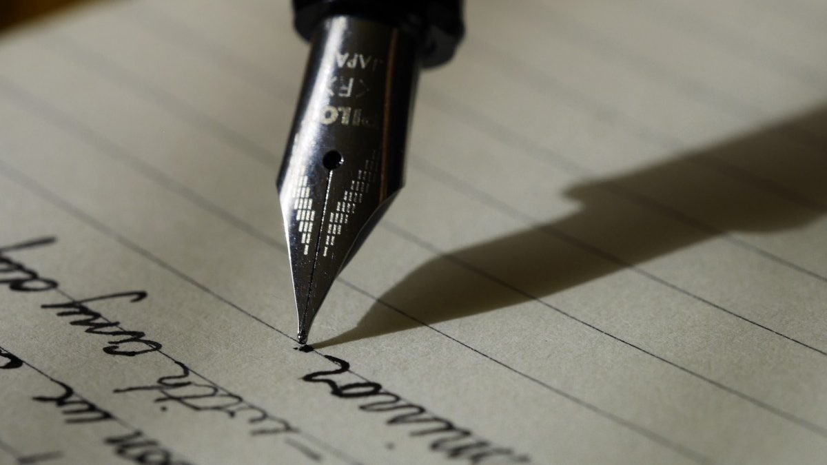 A pen, held mid-way through writing a sentence.