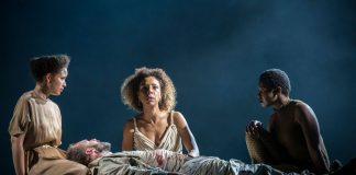 Cleopatra (Sophie Okonedo) kneels behind a dying Antony (Ralph Fiennes) flanked by two servants.