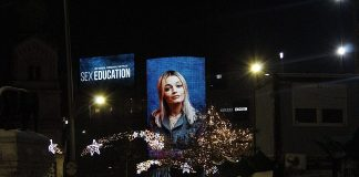 A board displaying the face of an actress from the television show Sex Education.