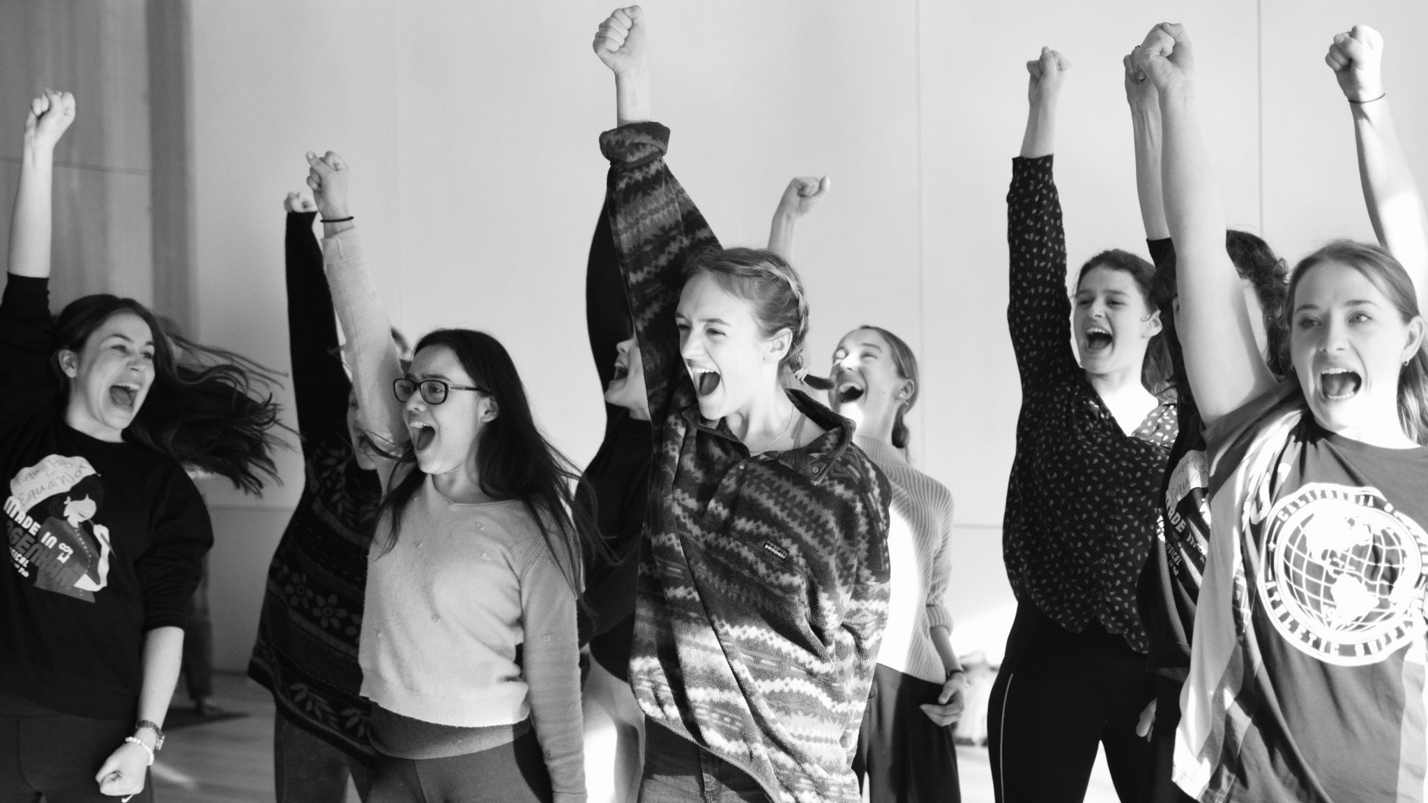 A group of actors in the musical Made in Dagenham mid-song, each with their right fist in the air