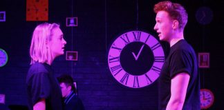 A woman and man stand facing each other with a clock in the background.