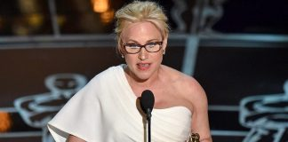 Patricia Arquette stands on stage with an Oscar statuette and a sheet of paper, speaking into a microphone.