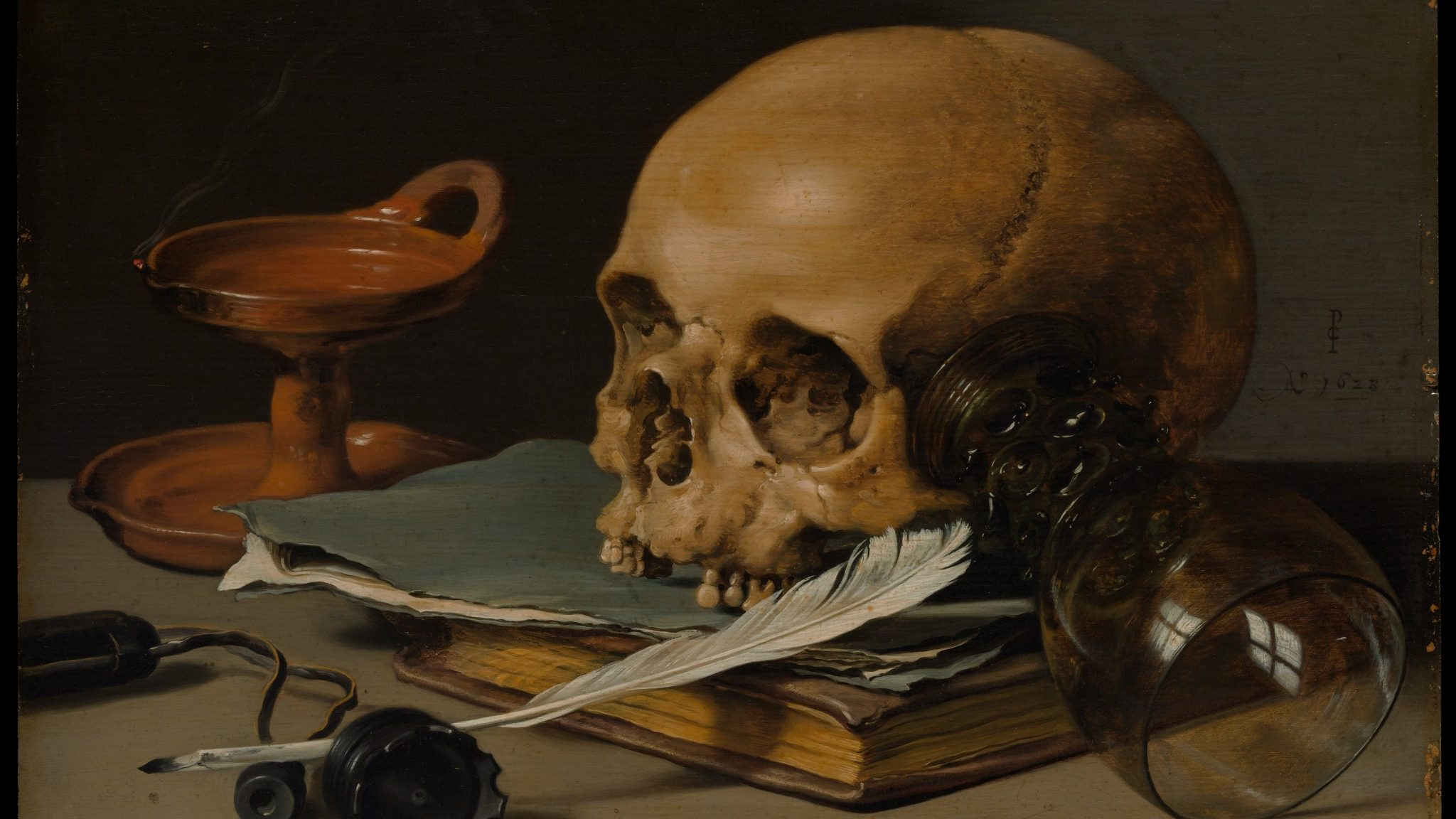 a painting of a skill, sat atop a desk, with a quill resting partly in its mouth.