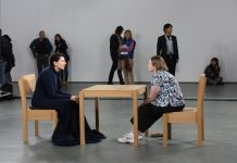 A lady in a black robe stares at another lady across a table.