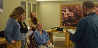 A group of four young women and a young man rehearsing a scene from a play. There is a picture of Oscar Wilde on a wall in the background