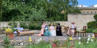 five woman dressed in old-fashioned upper class dresses sitting in a garden setting; there is a chaise long, a sofa and a table with chairs