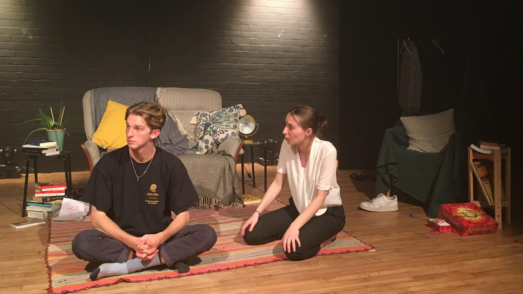 A young woman and man sitting on the floor in a living room; the man looks off to the side and the woman is looking at him