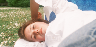 A person lies on a blanket in a field of flowers looking down towards the camera