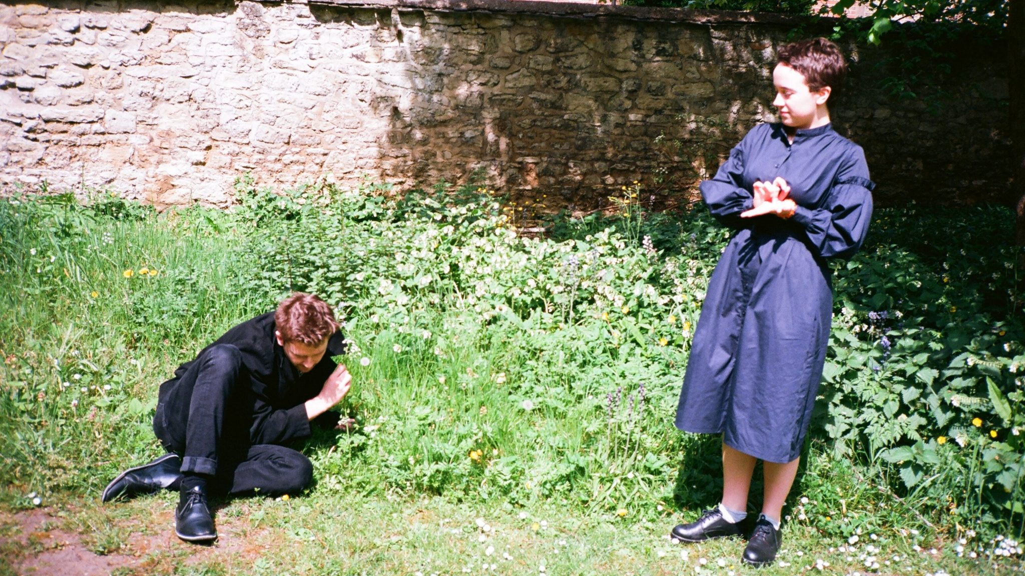 A man huddles on the grass with a woman looking over him
