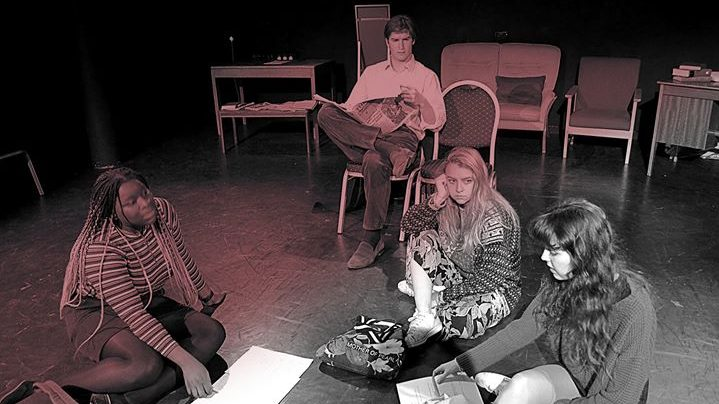 Three girls sit on the ground rehearsing a play, as a young man sitting on a chair looks on reading a newspaper
