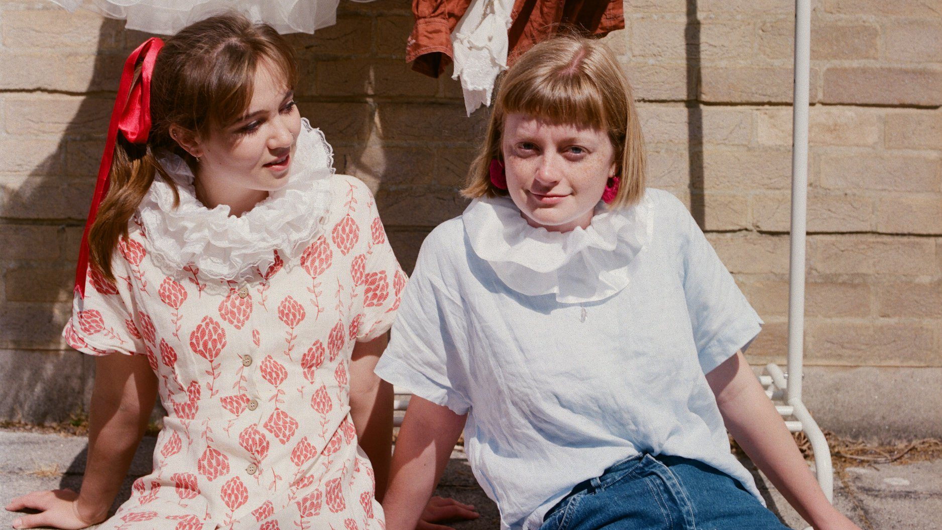 Two girls sit in front of a clothes rail, with white ruffles round their necks, one of them looking at the other