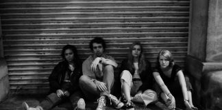 A black and white image of a group of four people casually sitting against a garage door