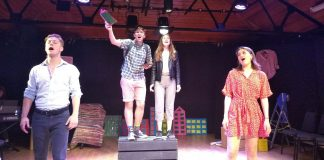 Two people stand on a box with two people either side, all of them are singing