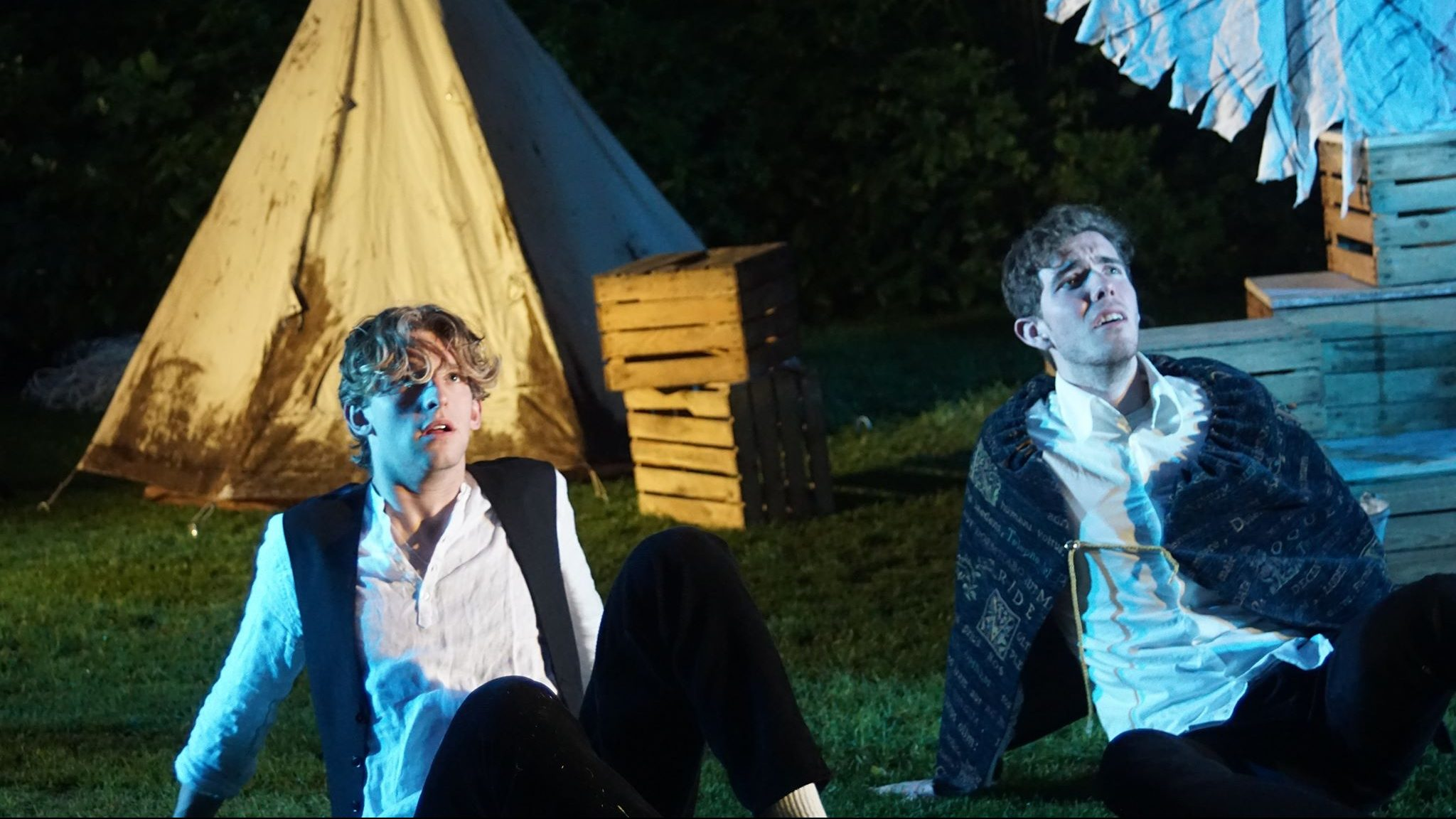 Two men sit on the floor in a blue light looking up with a tent behind them
