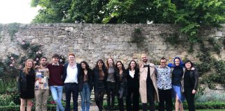The cast and crew of the play standing in a row in a garden setting with their arms around each other