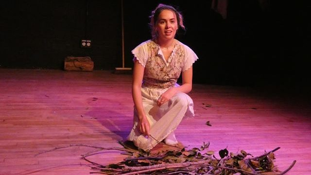 A young woman kneels down in front of a pile of sticks, twigs and leaves