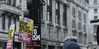 Anti-racism protestors in London stand holding 'say no to racism' signs.