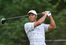 Tiger Woods, wearing a white shirt and cap, mid-drive against a background of green forest.