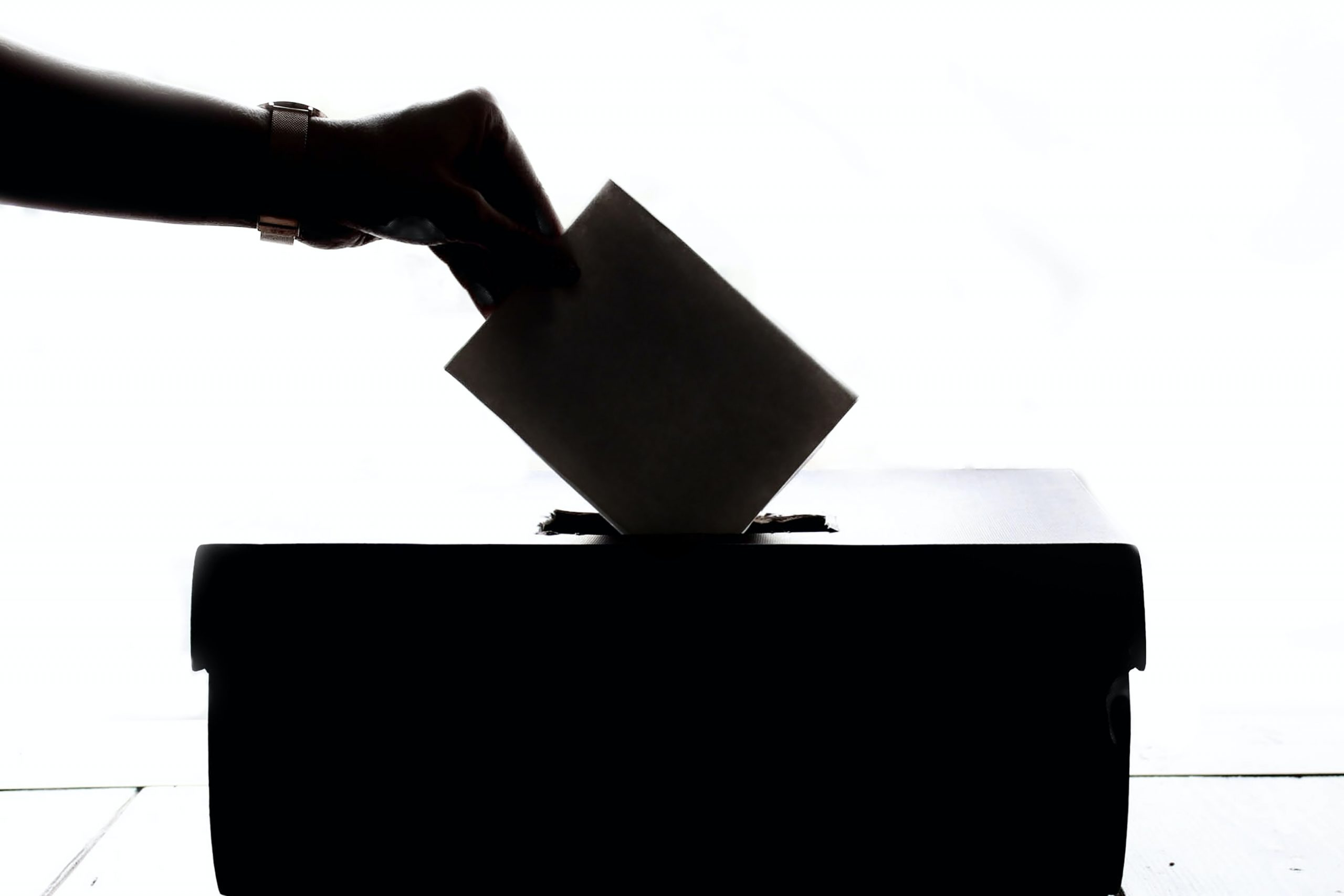 Silhouette of an arm putting an envelope into a box.