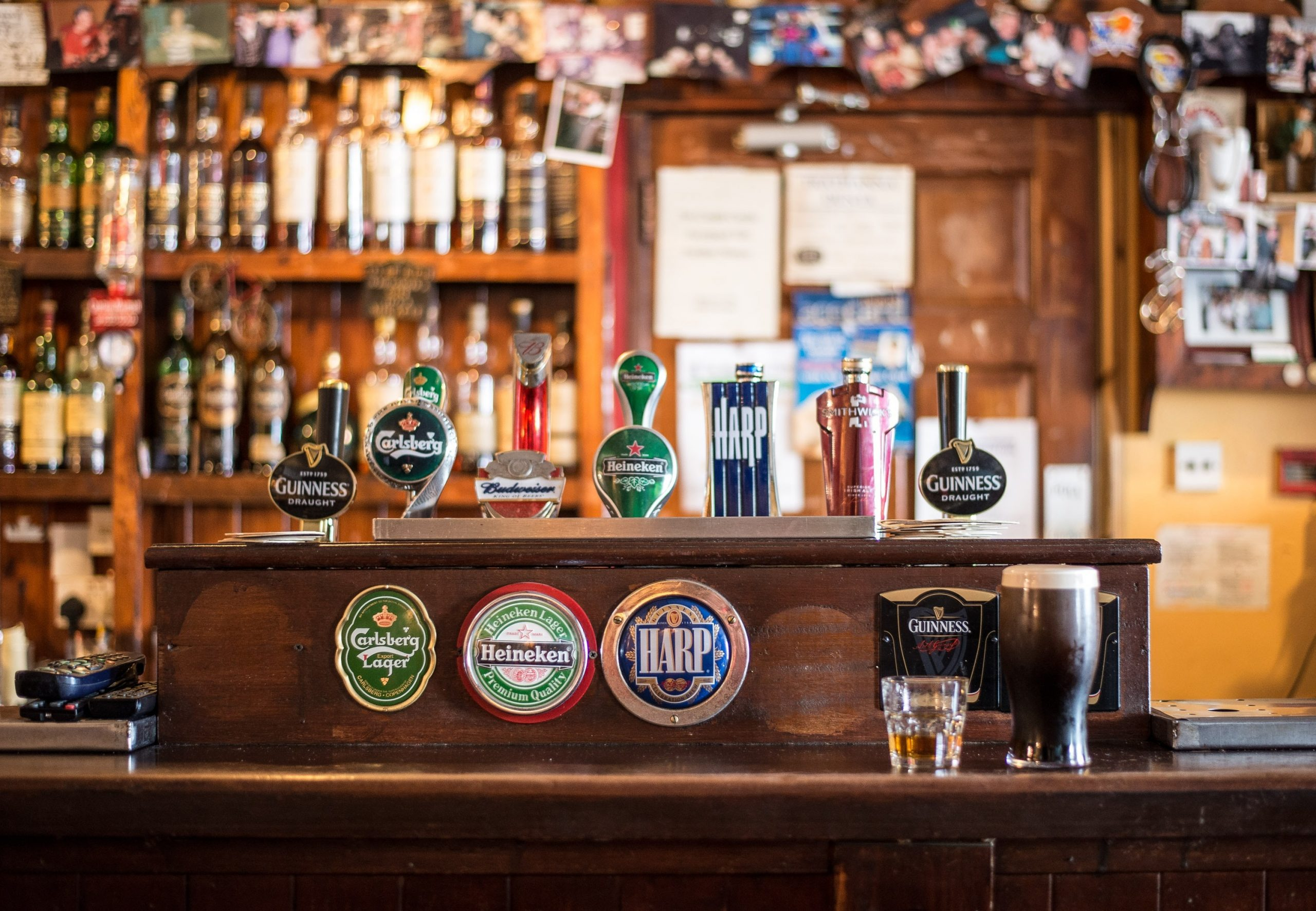 A traditional pub's beer taps behind its wooden counter.