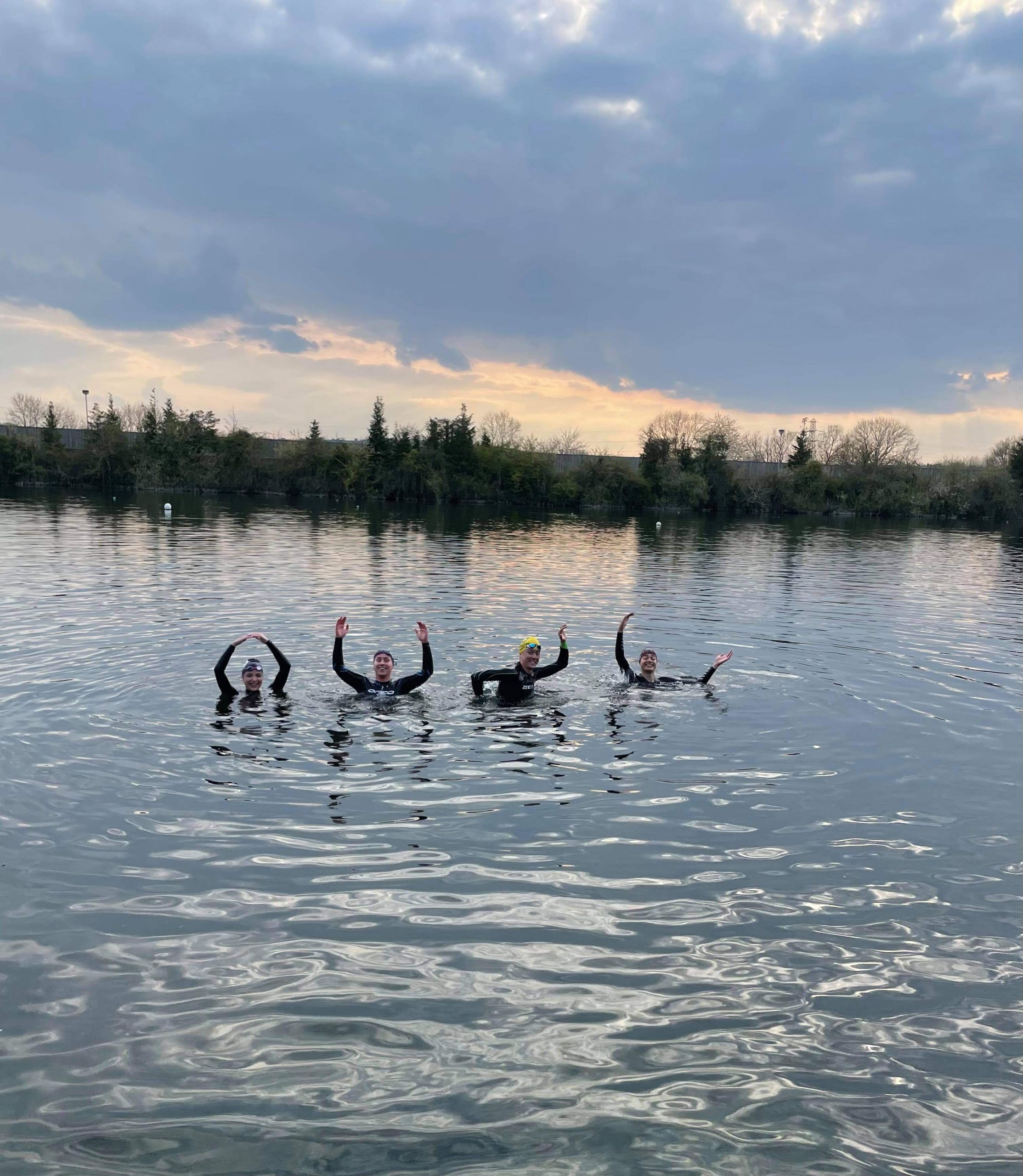 Four of the team's swimmers can be seen making the OUSC signs in the water during a training session