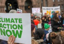 "A sign saying ""CLIMATE ACTION NOW"" on the left, with protestors in the background."