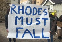 """A white banner being held up by two people who one are hidden behind it. In blue letters is written: """"RHODES MUST FALL"""""""