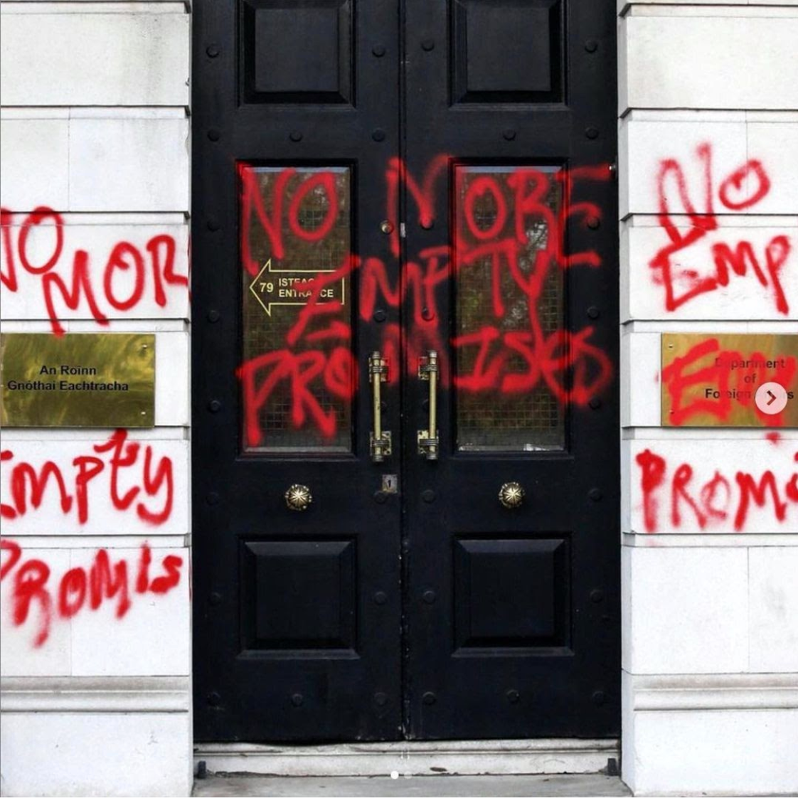 The door of the Department of Foreign Affairs in Dublin, Ireland, sprayed with red paint that spells out 'No More Empty Promises' three times.