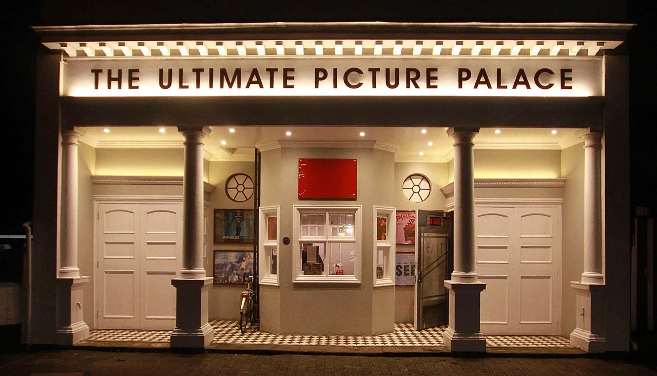 A cinema front, with the name written at the top is THE ULTIMATE PICTURE PALACE. There are two then pillars at the front, at between these two pillars in the ticket office. The cinema front is lit up.