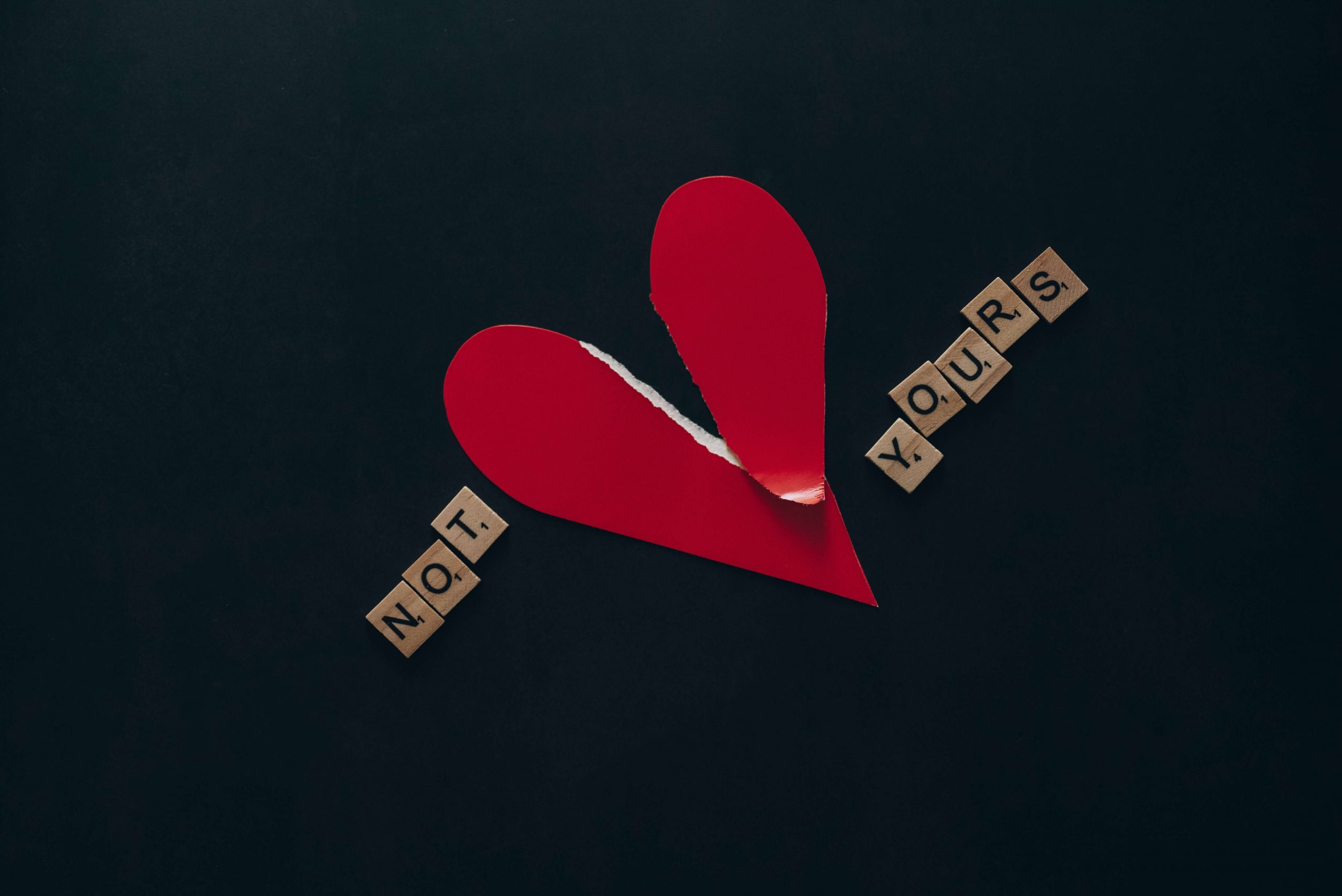 A ripped red paper heart on a dark blue background with the scrabble letters 'Not yours'.