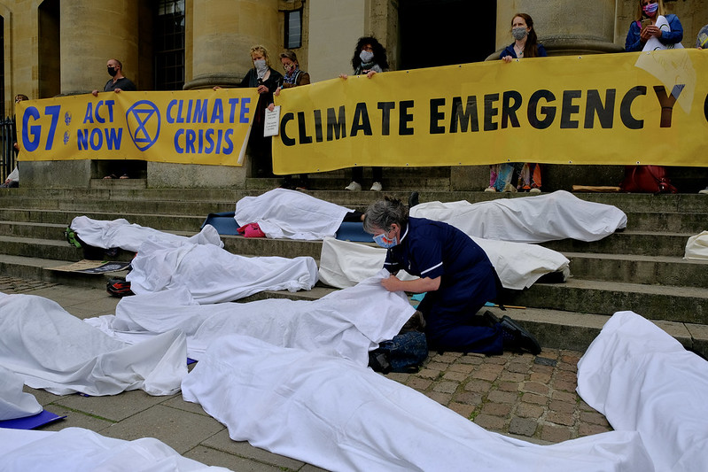 """ID: Around seven people lying on the ground completely covered in white sheets. Behind them to the right on steps stand protestors holding yellow banners which read: """"G7 / ACT NOW / 'XR LOGO' / CLIMATE CRISIS"""" and """"CLIMATE EMERGENCY""""."""