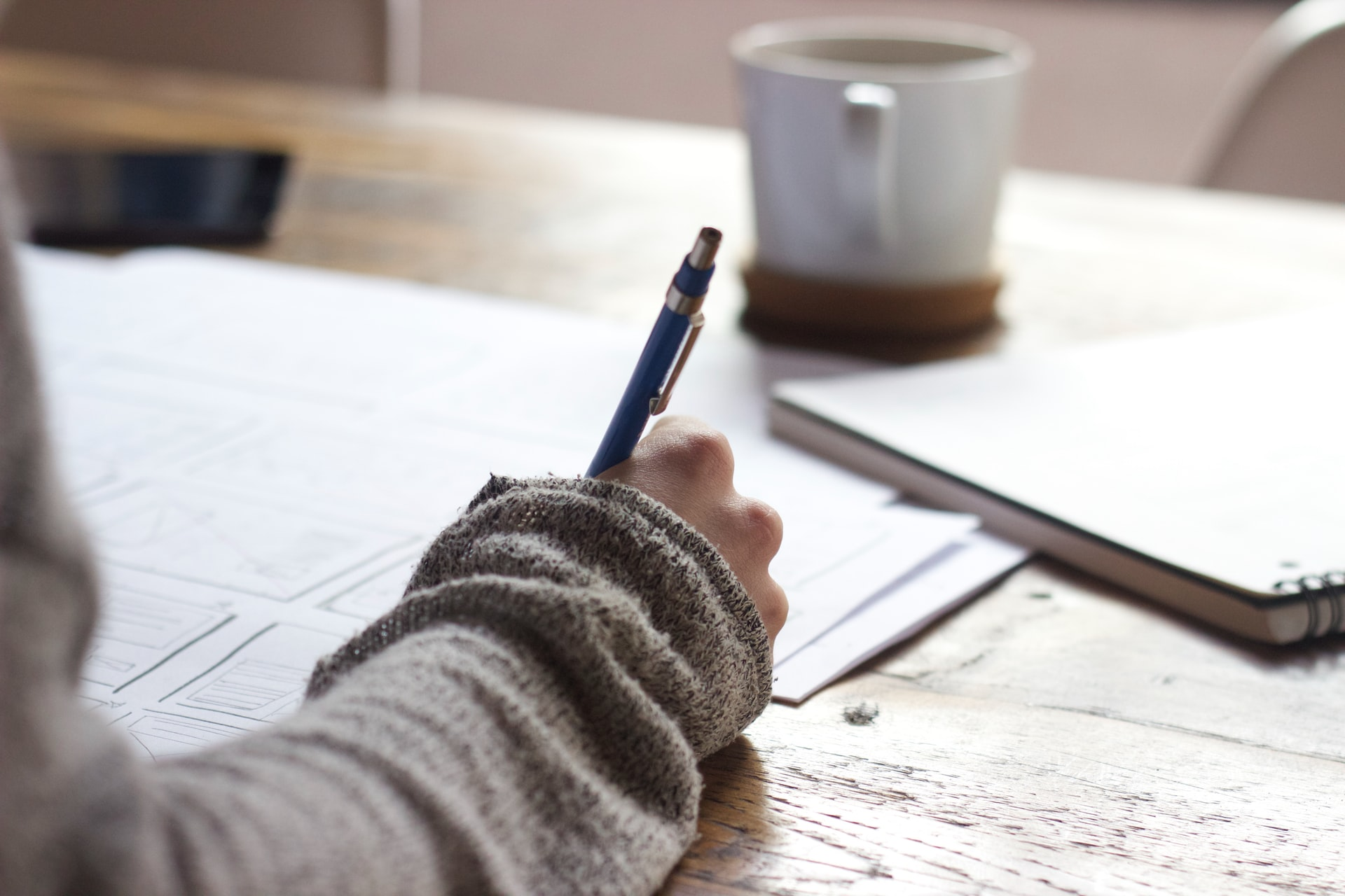 A close-up view of a desk with paper and a mug on it, and a person's arm holding a pen and making notes.