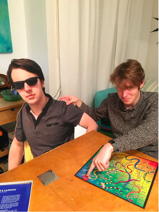 Two friends play snakes and ladders; one is a cardboard cut-out.
