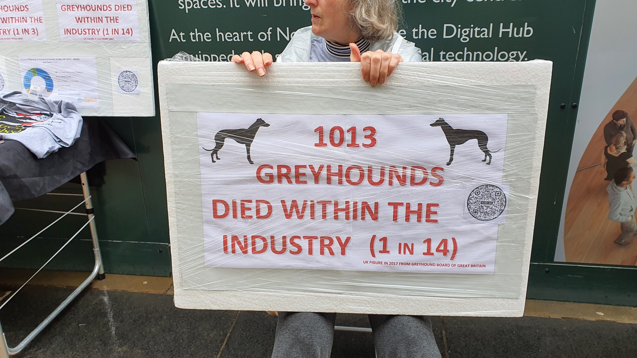 """A women holding a sign saying: """"1013 GREYHOUNDS DIED WITHIN THE INDUSTRY (1 in 14)"""" and in small writing at the bottom """"UK FIGURE IN 2017 FROM GREYHOUND BOARD OF GREAT BRITAIN"""""""