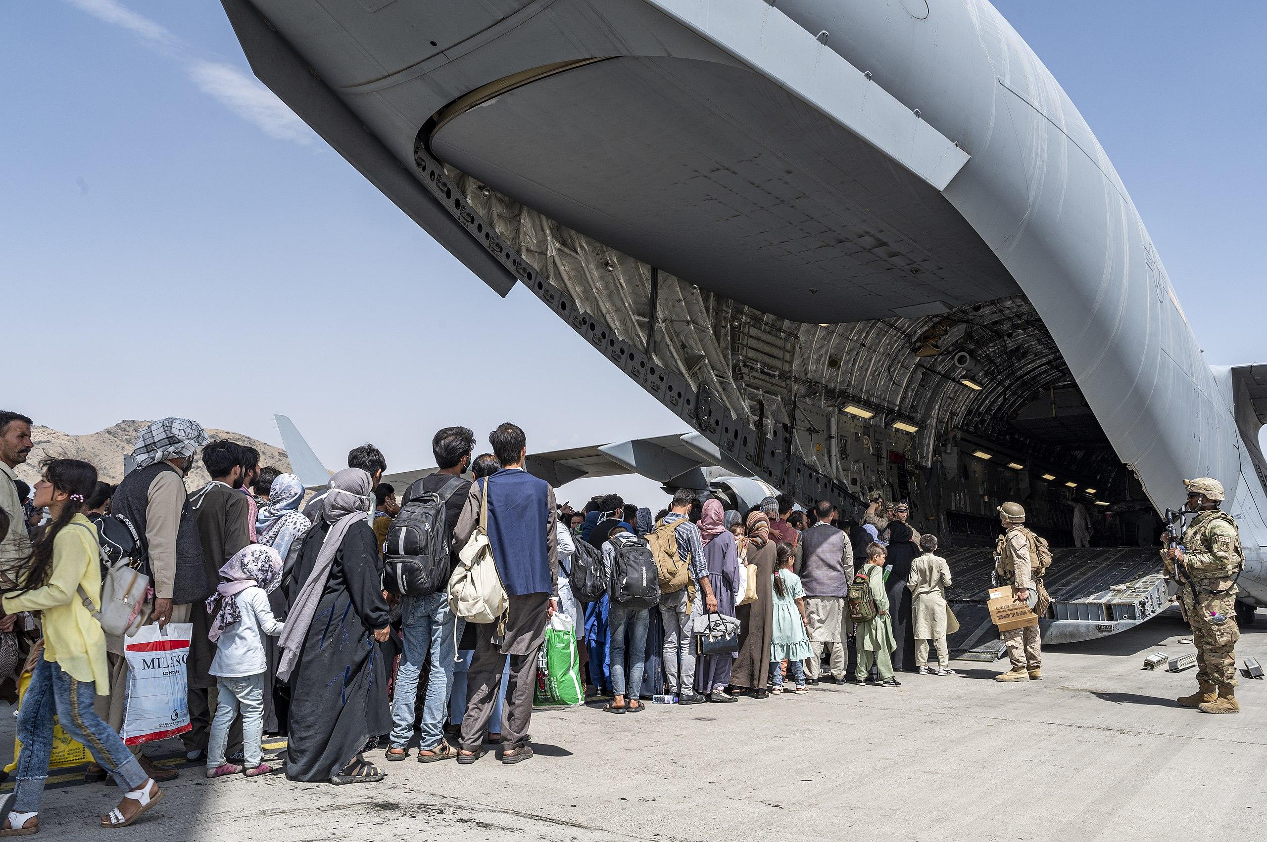 U.S. Airmen and U.S. Marines guide qualified evacuees aboard a U.S. Air Force C-17