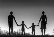 A naturalistic statue of a father, mother and two sons, all holding hands against a grey sky